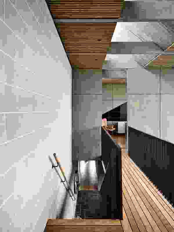 The second bedroom and ensuite are accessed via a long bridge that traverses the double-height volume.
