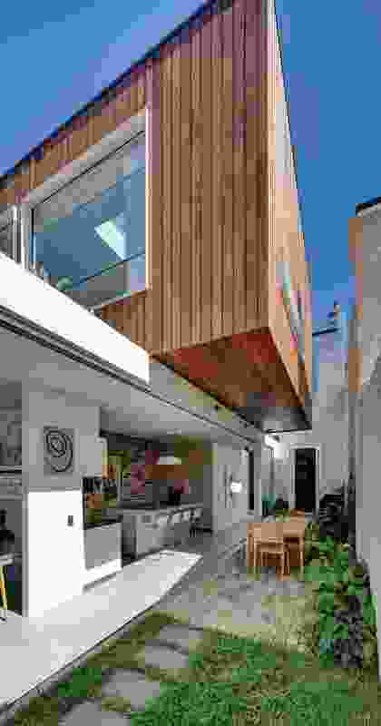 The timber-clad upper volume overhangs the courtyard space below. Artwork: Anne Richmond (foregound) and Chris Antico (background).