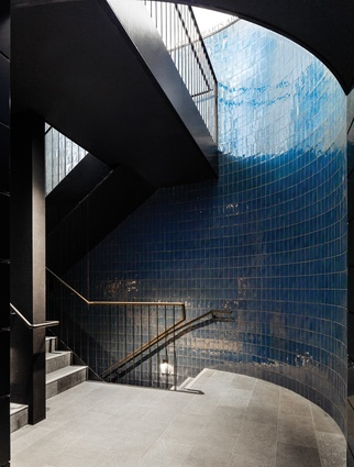 Glazed dark blue tiling creates an immersive experience within the intimately scaled space of the foyer.