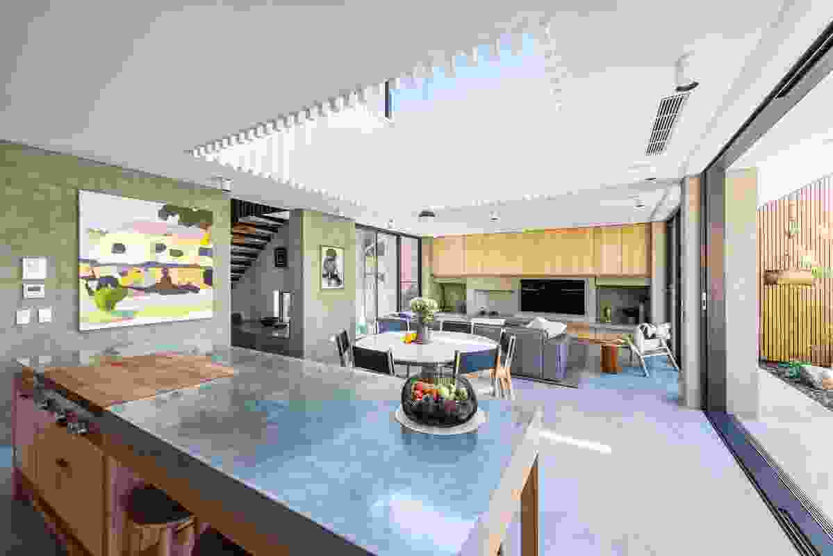 A void above the living areas lets plenty of light in, which is perfect for the owners, who spend a lot of time entertaining in the kitchen. Artwork: Michael Muir.