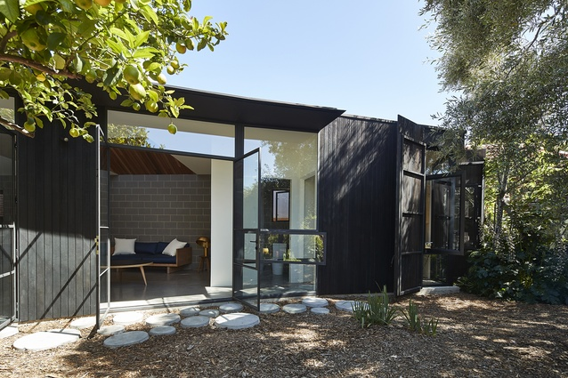 The charred timber exterior of the extension curves around an olive tree and recedes into the garden.