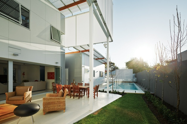 A double-height outdoor room mediates the temperature of both the upper and lower levels, with automatic blinds shading the house.
