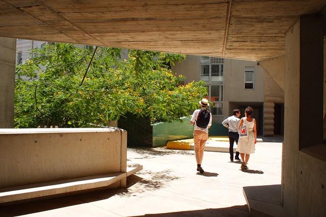 Entering the cool, leafy courtyard of Flores & Prats' Building 111, through the deep protective outer façade.