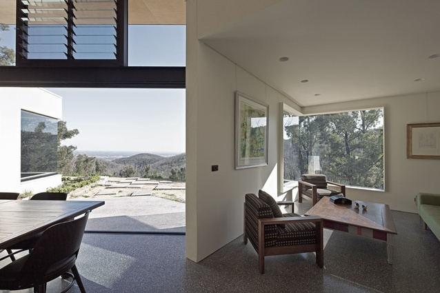 Large windows drape the interior in natural light and frame views of Kinglake National Park.