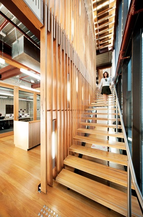 "A four-storey ""vertical street"" at the northern end of the building is a lively space with timber screens and steel stairs."