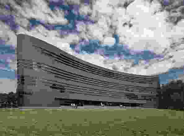 弯曲的,单一的形式,占据了校园的东南角,作为毗邻的椭圆形的看台般的背景。