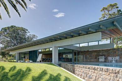 A wall of local stone, broken with blackbutt in shaded areas, acts as a spine, stitching together the house and landscape as one.