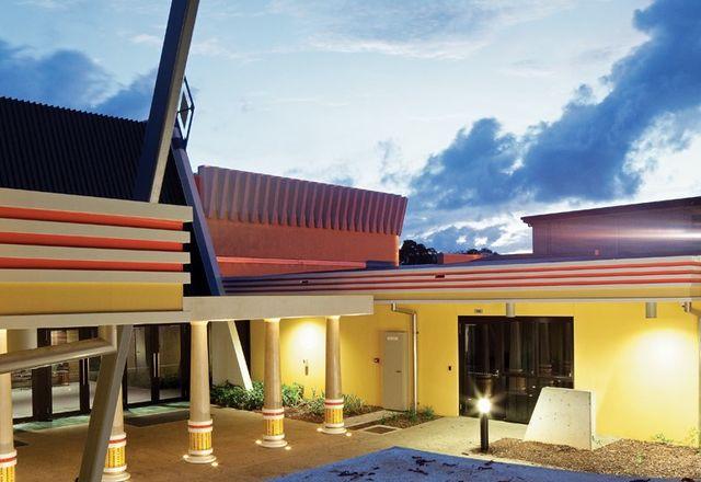 """入口两侧是两个现有的倾斜混凝土""""扶壁""""。一个由五根柱子支撑的天篷。"""