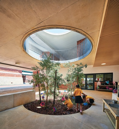 Three indigenous trees grow through a large circular opening, which visually links the generous verandah areas on both levels.