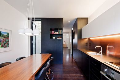 Black laminate joinery with subtle lighting and a single sheet of copper for the splashback. Artwork: Karl Maughan.