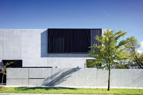 A bold, largely windowless facade caters to the clients' love of concrete and desire for privacy.
