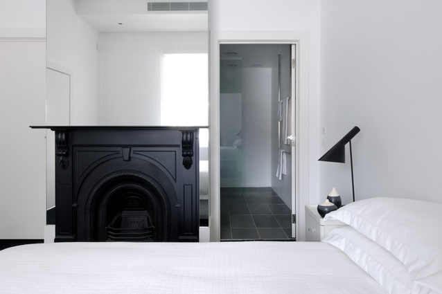 The monochromatic master bedroom is fitted with floor-to-ceiling mirrors around the existing fireplace.