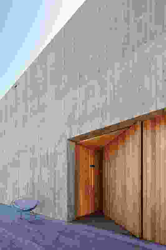 A pivot timber door marks the south-facing entry within the textured in situ concrete wall.