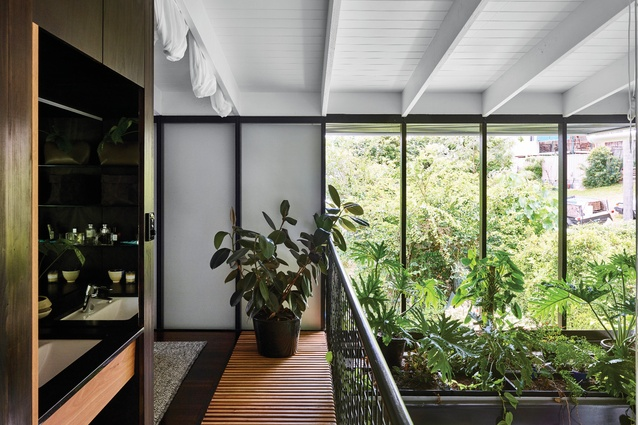 Framed by a suspended bed of lush plants, the large void provides connection between the upper and lower levels.