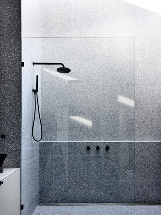 "The luxurious ensuite is a ""marvel of delicate grey terrazzo,"" illuminated by the skylight above."