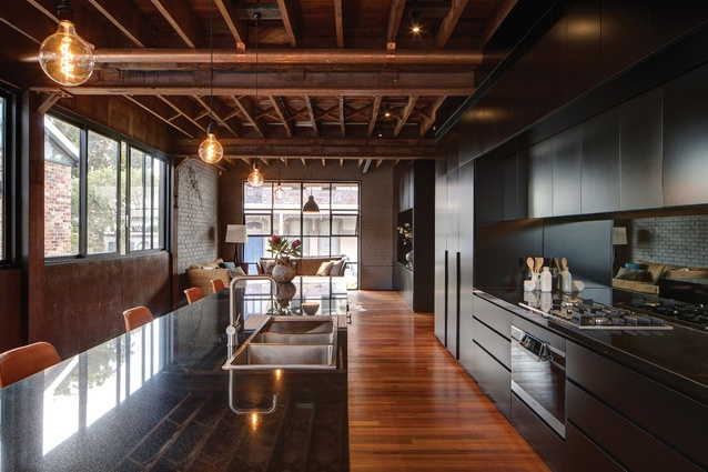Characterized by an interplay between factory materials and sympathetic additions, the kitchen connects the main living spaces.