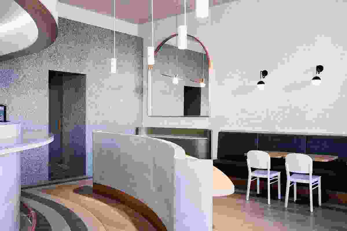 The cafe has a series of pendant light clusters. Each plays a role in sectioning the large space.