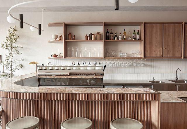 """这家大型弯曲咖啡厅以""""金色卡布奇诺""""大理石、黄铜镶边和凹槽木镶板为特色。"""