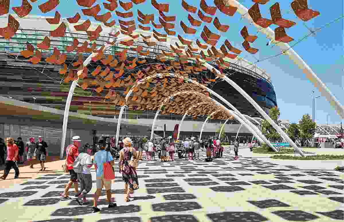 An arbour of parabolic steel arches adorned with a tensile artwork directs pedestrian traffic through the site.