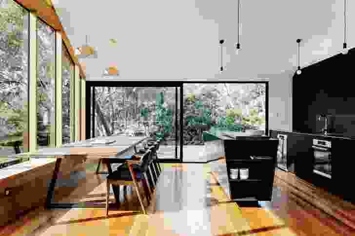 Blackened timber in the kitchen mirrors the dark external palette, which reduces visibility from a distance.