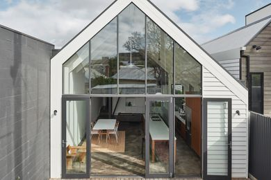 Double-height glazing at the house's southern end lets in ample light. The house extends onto a small but useful courtyard.