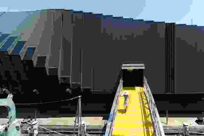 A yellow ramp, reminiscent of a gangway used to board and disembark from a ship, provides a connection from the Waterfront Pavilion to one of the vessels.