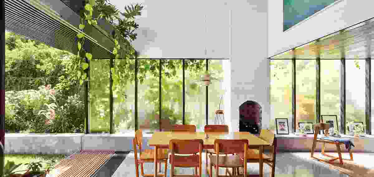 Frosted glass washes the space in gentle daylight while allusively smudging the image of a boundary garden onto the interior surface.