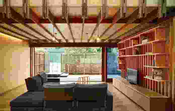 The lines of the exposed ceiling beams are echoed in both the joinery and the private grille that wraps the courtyard.