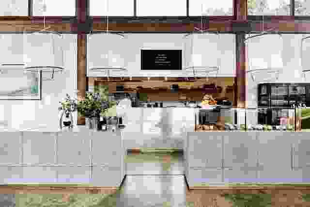 酒吧和柜台构成了开放式厨房的框架,并以斑点灰色水磨石和漂浮的白色吊灯为特色。