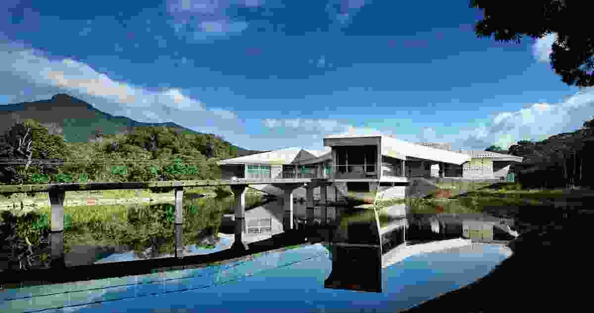 Located at Cape Tribulation, Stamp House is a concrete residence with six pods dramatically cantilevered over a lake.