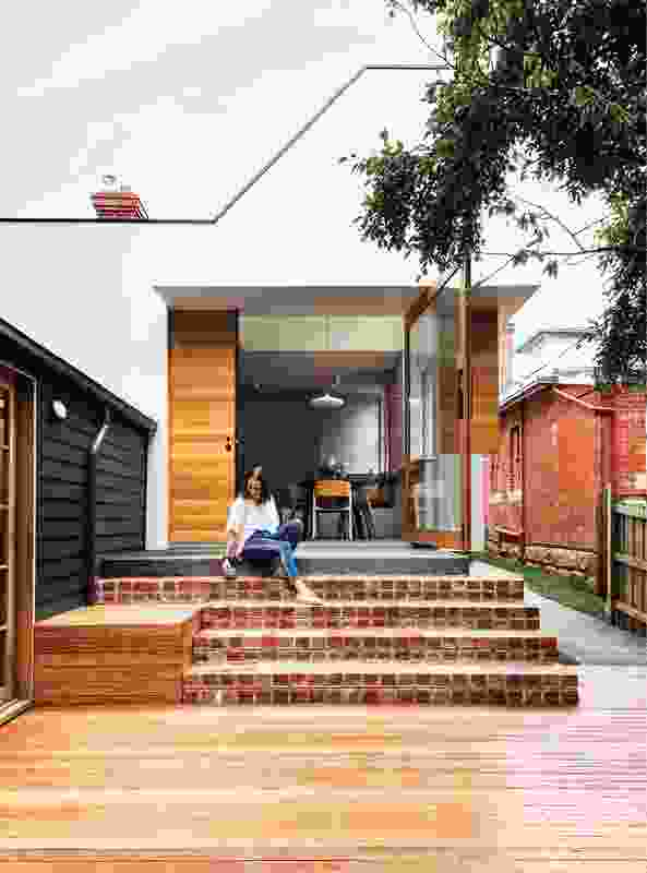 Echoing the character of the surrounding context, reclaimed brick stairs connect the home to the garden.