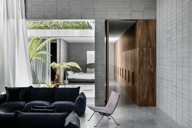 The living space and main bedroom open onto a courtyard garden of swamp banksia and Australian tree ferns.
