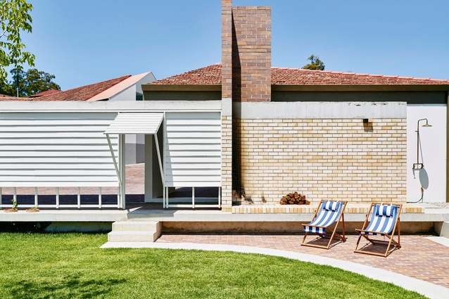 An open-air brick fireplace at the end of the garden sits adjacent to a swimming pool.