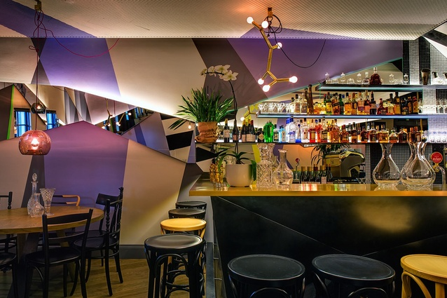 A black metal bar with a brass top welcomes visitors into the downstairs bistro.