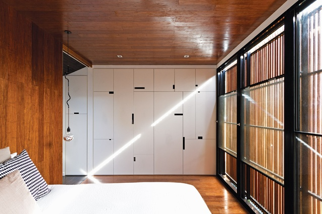 Sunlight streams into the main bedroom, which provides a filtered view of the courtyard.
