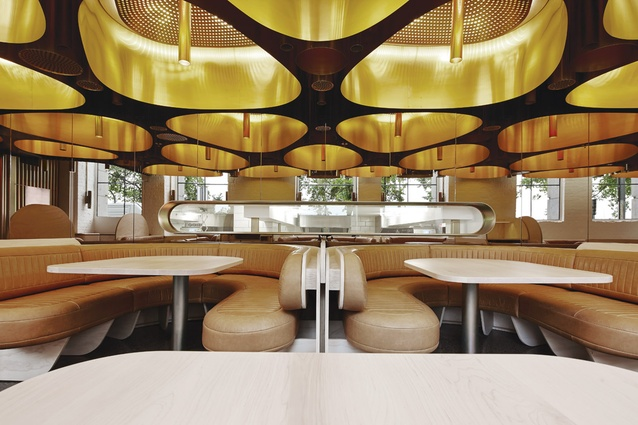 Natural leather banquettes and blond  rock maple tabletops imbue the space with  a sense of luxury.