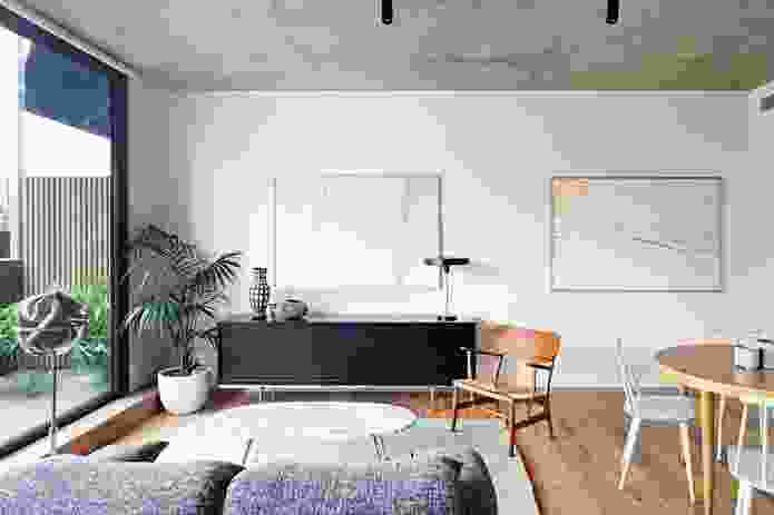 White walls, concrete ceilings and timber floors contribute to a restrained but elegant character. Artwork: Brooke Holm.