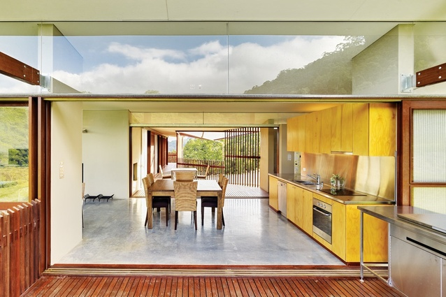 A plywood kitchen extends out onto a barbecue zone.