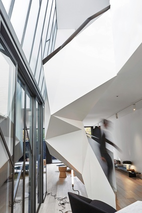 A faceted steel stair spirals up through a void at the centre of the open-plan living area.