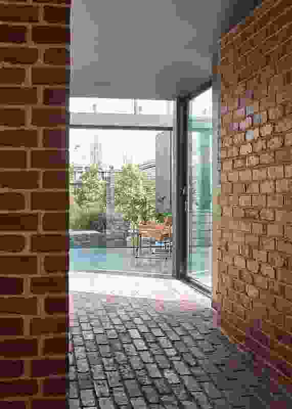 "A heavily textured brick ""tunnel"" connects old and new; entering the bright new space from here makes for a grand reveal."