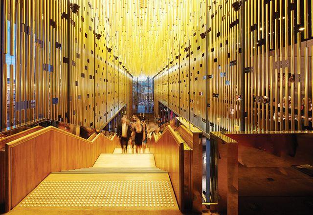 在金色阳极氧化铝管的窗帘下,楼梯上升到主剧院。
