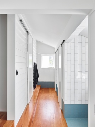 Vertically laid gloss white tiles work in juxtaposition to the original white weatherboards.