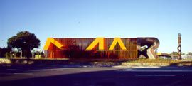 "A small building built on a massive scale, the Marion Cultural Centre asserts a strong urban and political identity partly though marking the place's name within the fabric of the building and landscape. The ""MAR"" is writ large across the eastern street elevation. The ""I"" is formed by the sculpture to the right of the building by Greg Johns."