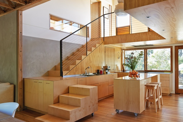 The plywood stair uses the kitchen bench as a landing, and the first three steps are a mobile unit on wheels.