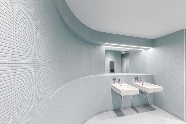 Curved walls in the bathrooms reference the curves of the entry stairway.